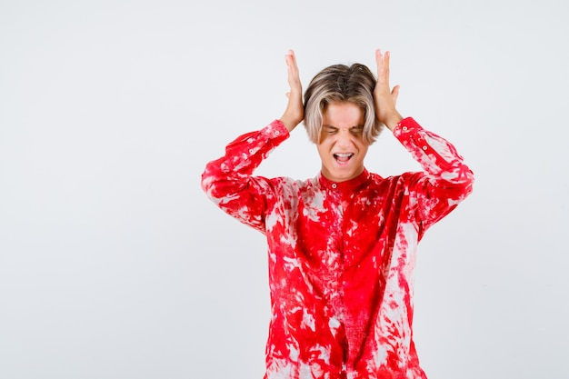 Teen blonder mann im übergroßen hemd mit den händen auf dem kopf und sieht schmerzhaft aus, vorderansicht.