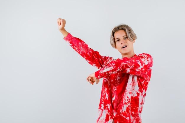Teen blonder mann in übergroßem hemd, der den oberkörper streckt und müde aussieht