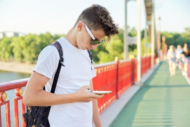Teen boy 15, 16 jahre alt mit sonnenbrille modischen haarschnitt mit smartphone, outdoor, sonnenuntergang sommertag auf fußgängerbrücke, kopie raum