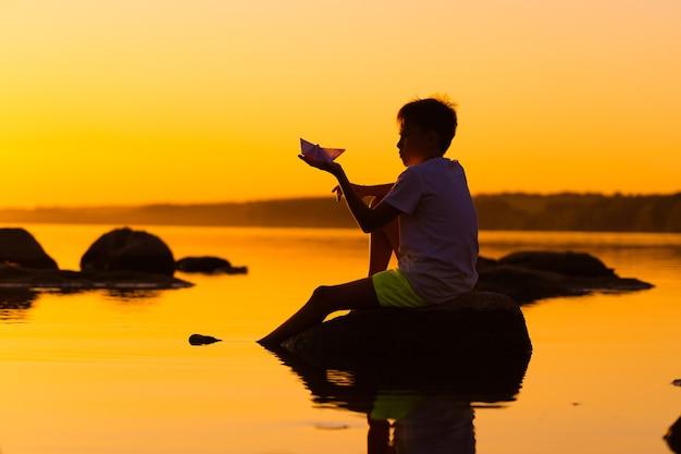 Teen boy betrachtet papierflieger in der hand bei orangefarbenem sonnenuntergang. eine silhouette eines kindes mit origami-flugzeug gegen wasser. selektiver fokus