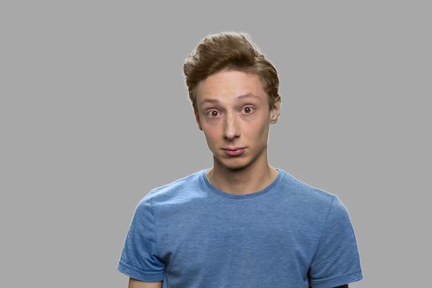 Teen boy, der kamera mit überraschungsausdruck betrachtet. porträt des verwirrten jugendlichen kerls, der gegen grauen hintergrund steht.