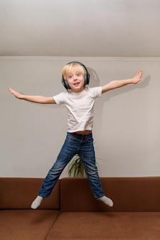 Teen boy, der musik auf kopfhörern hört und auf couch springt.