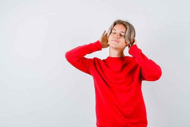 Teen boy hält die hände auf dem kopf, schließt die augen im roten pullover und sieht charmant aus. vorderansicht.
