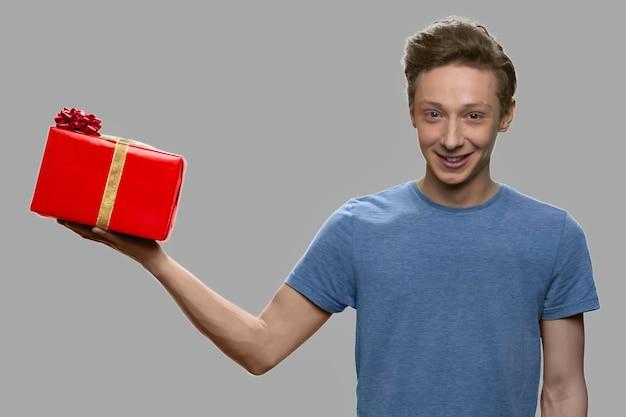 Teen boy hält geschenkbox auf seiner handfläche. porträt des schönen kaukasischen jungen mit geschenkbox gegen grauen hintergrund.