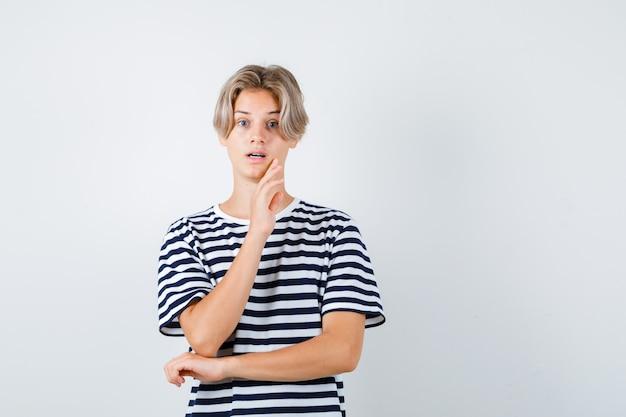 Teen boy hält hand am kinn im t-shirt und sieht besorgt aus. vorderansicht.