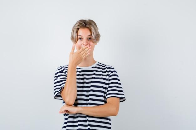 Teen boy hält hand auf mund im t-shirt und schaut erstaunt. vorderansicht.