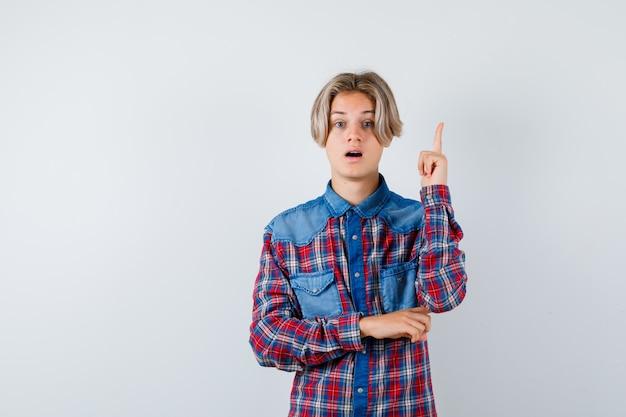 Teen boy im karierten hemd zeigt nach oben und schaut perplex, vorderansicht.
