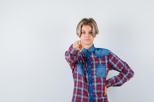 Teen boy im karierten hemd zeigt nach vorne und sieht selbstbewusst aus, vorderansicht. Premium Fotos