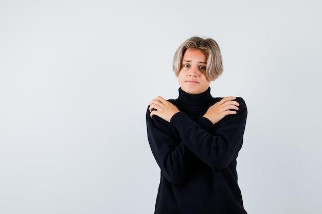 Teen boy im schwarzen pullover hält sich selbst und schaut verärgert, vorderansicht.