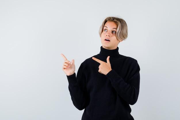 Teen boy im schwarzen pullover zeigt mit den fingern nach oben und sieht überrascht aus, vorderansicht.
