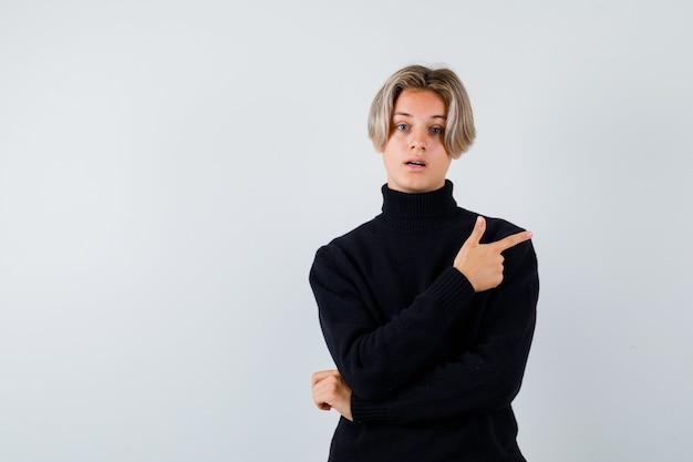 Teen boy im schwarzen pullover zeigt nach oben und sieht überrascht aus, vorderansicht.