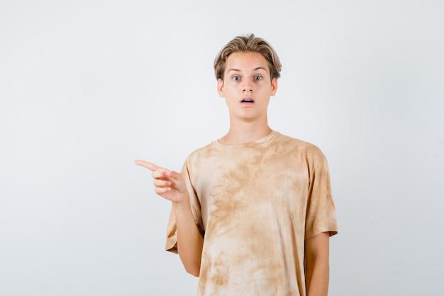 Teen boy im t-shirt, das auf die linke seite zeigt, den mund öffnet und schockiert aussieht, vorderansicht.