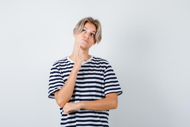 Teen boy im t-shirt, das den finger am kinn hält und nachdenklich aussieht, vorderansicht.