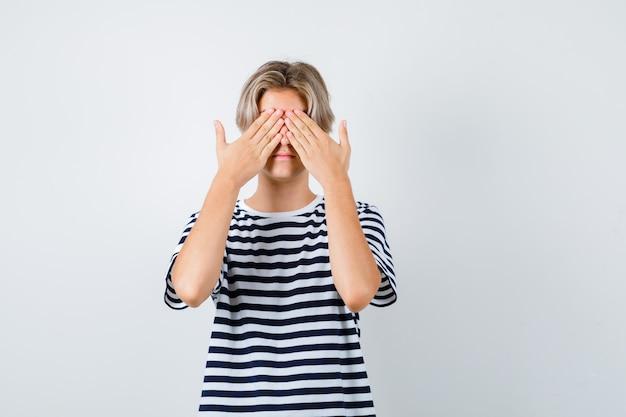 Teen boy im t-shirt, das die augen mit den händen bedeckt und verängstigt aussieht, vorderansicht.