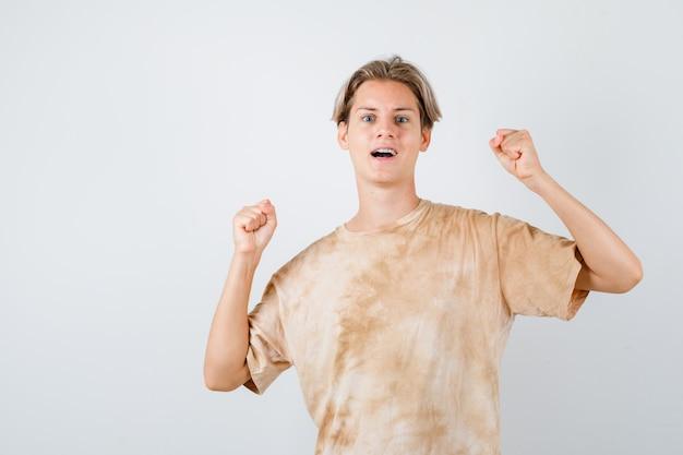 Teen boy im t-shirt, das gewinnergeste zeigt und siegreich aussieht, vorderansicht.