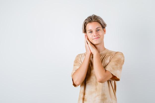 Teen boy im t-shirt, das sich auf palmen als kissen stützt und fröhlich aussieht, vorderansicht.