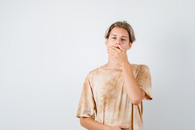 Teen boy im t-shirt gähnt, während er die hand auf den mund hält und schläfrig aussieht, vorderansicht.