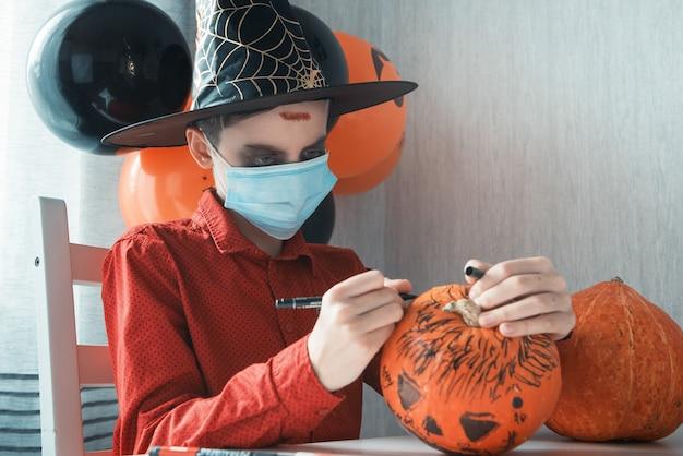 Teen boy in kostüm- und gesichtsmasken zum schutz gegen covid-19 beim zeichnen eines kürbises für die halloween-feier