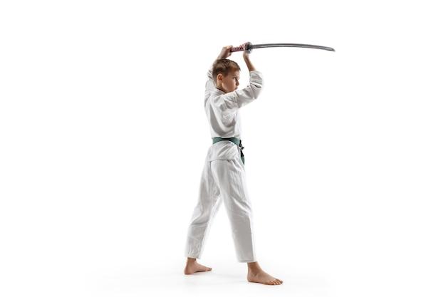 Teen boy kämpft am aikido-training in der kampfkunstschule. gesunder lebensstil und sportkonzept. kämpfer im weißen kimono auf weißer wand. karate-mann mit konzentriertem gesicht in uniform.