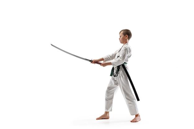 Teen boy kämpft beim aikido-training in der kampfkunstschule. gesunder lebensstil und sportkonzept. kämpfer im weißen kimono auf weißer wand. karatemann mit konzentriertem gesicht in uniform.