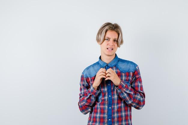 Teen boy mit händen auf der brust im karierten hemd und unzufrieden aussehend, vorderansicht.