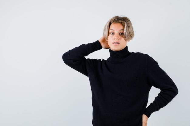 Teen boy mit hand an hals und taille im schwarzen pullover und verwirrt, vorderansicht.