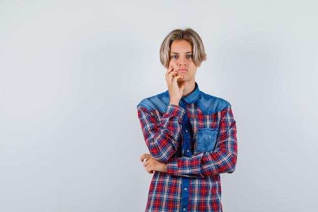 Teen boy mit hand auf wange im karierten hemd und traurig aussehend. vorderansicht.