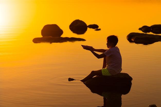 Teen boy mit origami-schiff in den händen. junge, der auf felsen nahe fluss sitzt. schöner orangefarbener sonnenuntergang. origami. fluss. see. sommerberufung