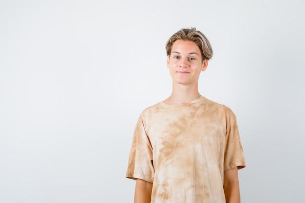 Teen boy posiert beim betrachten der vorderseite im t-shirt und sieht zufrieden aus. vorderansicht.