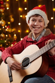 Teen boy spielt gitarre und sitzt in der nähe von geschmücktem weihnachtsbaum mit lichtern