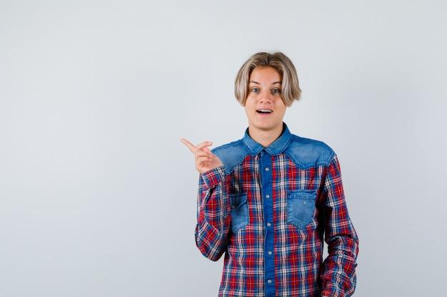 Teen boy zeigt auf die obere linke ecke im karierten hemd