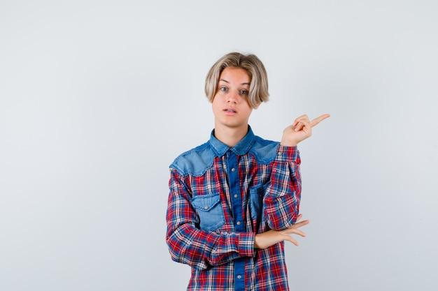 Teen boy zeigt auf die obere rechte ecke im karierten hemd und schaut vorsichtig, vorderansicht.