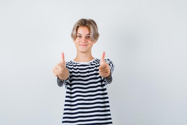 Teen boy zeigt daumen hoch im t-shirt und sieht fröhlich aus. vorderansicht.