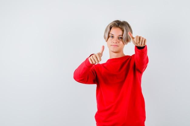 Teen boy zeigt daumen im roten pullover und sieht zufrieden aus. vorderansicht.