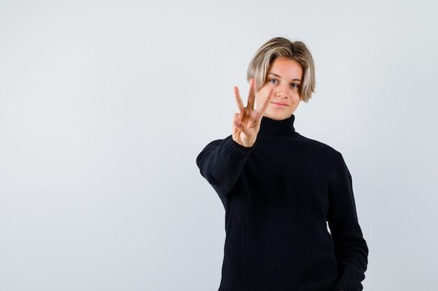 Teen boy zeigt drei finger im schwarzen pullover und sieht süß aus, vorderansicht.