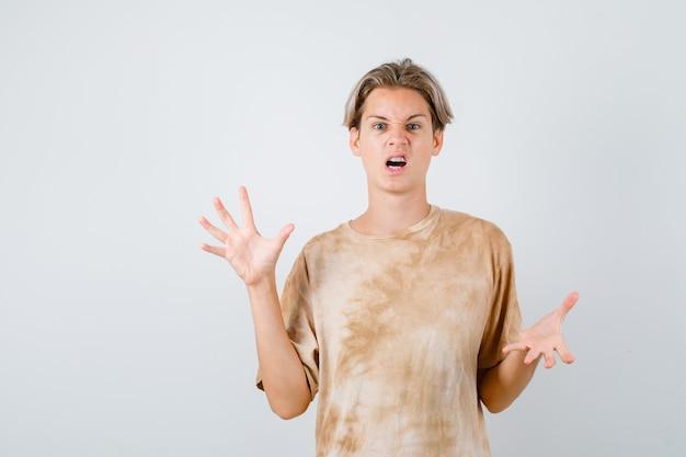 Teen boy zeigt krallen, die eine katze im t-shirt imitieren und aggressiv aussehen. vorderansicht.