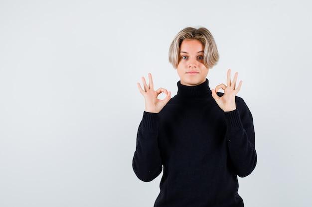 Teen boy zeigt ok geste im schwarzen pullover und sieht friedlich aus, vorderansicht.
