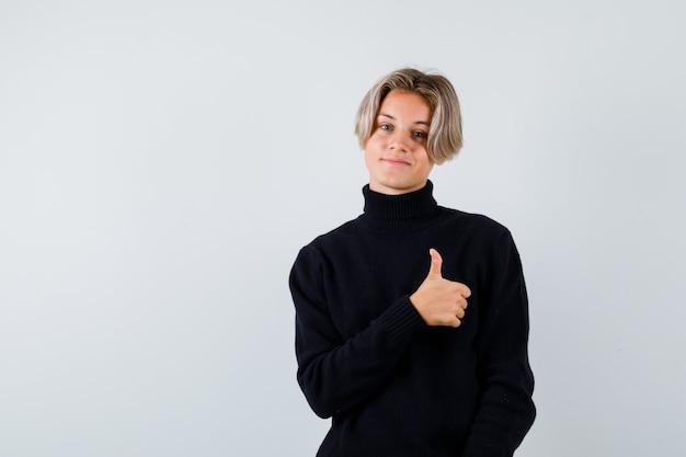 Teen boy zeigt ok geste im schwarzen pullover und sieht zufrieden aus, vorderansicht.