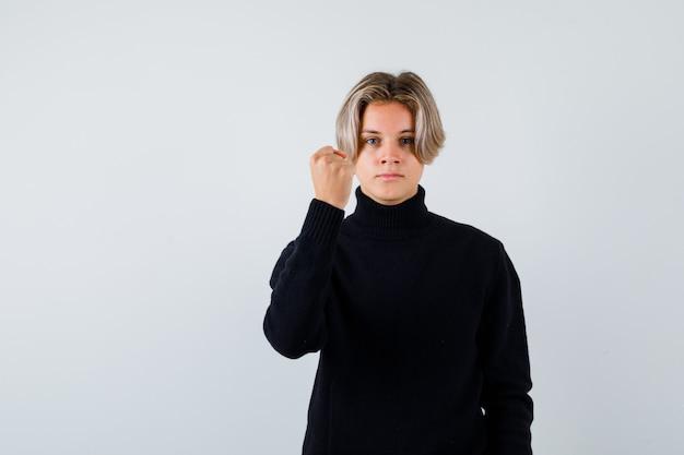 Teen boy zeigt siegergeste im schwarzen pullover und sieht ernst aus, vorderansicht.
