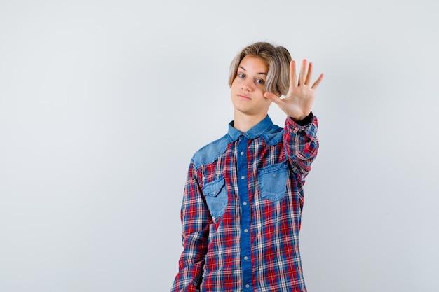 Teen boy zeigt stop-geste im karierten hemd und sieht selbstbewusst aus. vorderansicht.