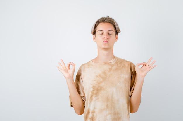 Teen boy zeigt yoga-geste, schmollende lippen im t-shirt und sieht friedlich aus, vorderansicht.
