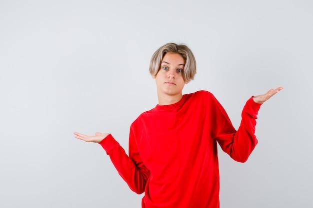 Teen boy zuckt mit den schultern im roten pullover und sieht unentschlossen aus. vorderansicht.