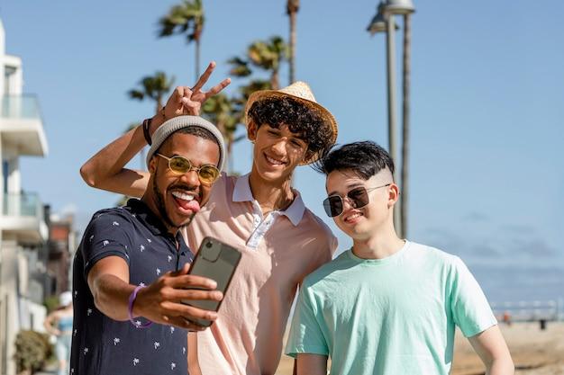 Teen boys machen selfie und genießen den sommer zusammen im freien in venice beach, los angeles