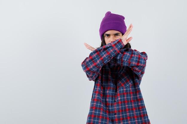 Teen frau hält zwei arme verschränkt und gestikuliert x zeichen ooking ernst