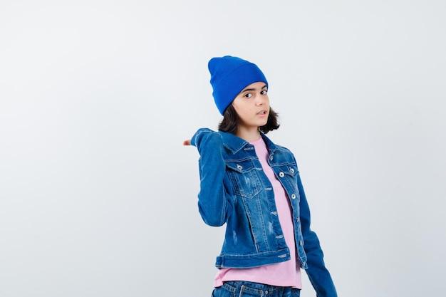 Teen frau zeigt beiseite und schaut über die schulter in rosa t-shirt, das ernst aussieht
