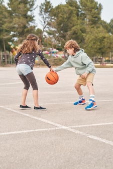 Teen freunde spielen zusammen basketball