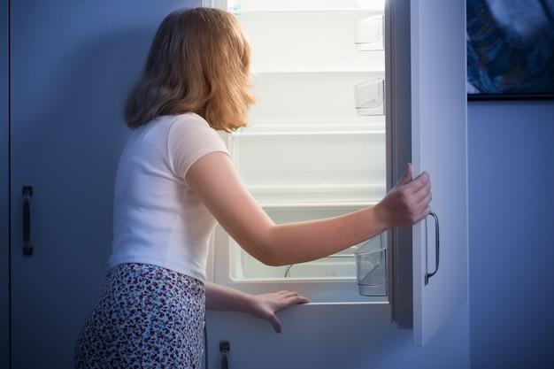 Teen girl am leeren kühlschrank