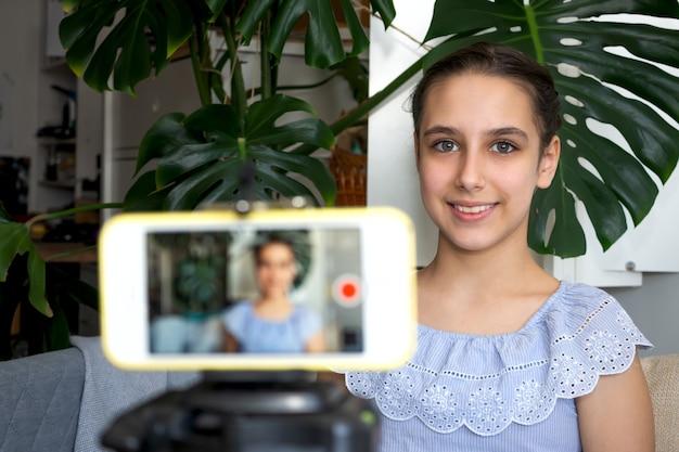 Teen girl blogger influencer aufnahme des video-blog-konzepts, das zu hause auf dem smartphone auf einem stativ spricht. teenager-social-media-vlogger, der vlog dreht und online-podcast auf dem handy streamt.