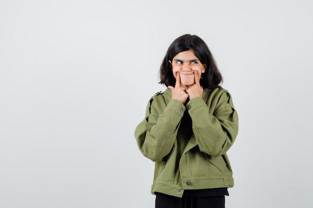 Teen girl erzwingt ein lächeln im gesicht in t-shirt, jacke und sieht gelangweilt aus. vorderansicht.