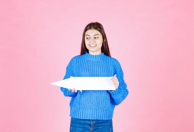 Teen girl hält einen pfeil aus papier als zeiger beiseite.